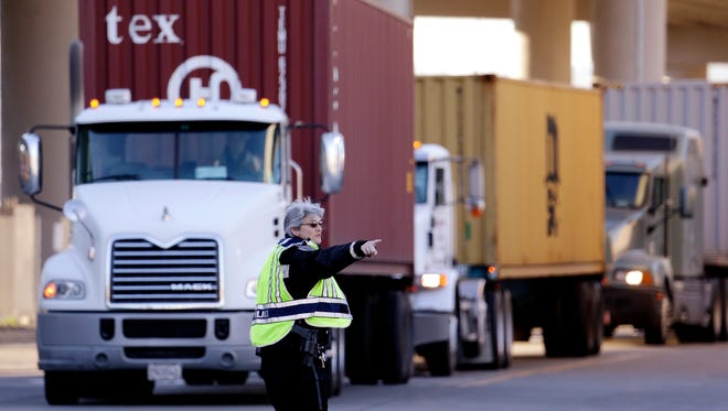 Seattle police officer Carol Castellani directs loaded container trucks to an entrance at the Port of Seattle Tuesday, Feb. 17, 2015, in Seattle. Seaports in the U.S. West Coast that were all but shut over the weekend because of a contract dispute are reopening as the nation's top labor official tries to solve a stalemate between dockworkers and their employers that already has disrupted billions of dollars in U.S. international trade. U.S. Labor Secretary Thomas Perez plans to meet Tuesday in San Francisco with negotiators for both the dockworkers' union and the maritime association, which represents shipping lines that carry cargo and port terminal operators that handle it once the ships dock. (AP Photo/Elaine Thompson)
