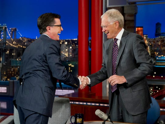 """Comedy Central's Stephen Colbert, left, shakes hands with host David Letterman on the set of the """"Late Show with David Letterman,"""" in New York. Earlier in April, Letterman announced his retirement in 2015 and CBS announced Colbert as his replacement."""