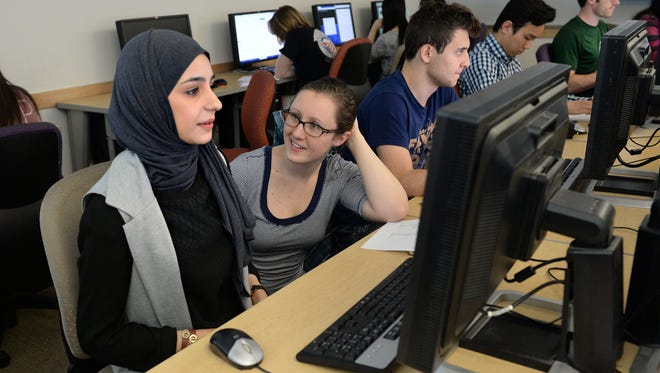 Computer Science teaching assistant Gareth Halladay assists Fatima Altimimi in a computer science class at Colorado State University on Thursday, April 14, 2016. During the most recent 2014-2015 school year, only 13 percent of graduates from the Computer Science Department were women.