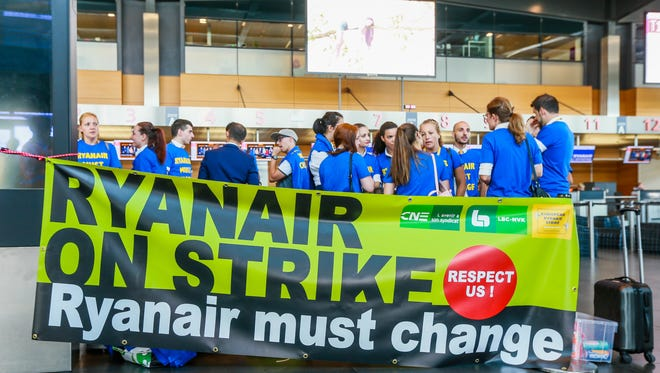 Employees of low-cost airline Ryanair gather behind a banner as they strike at the Charleroi airport in Belgium on July 25, 2018.