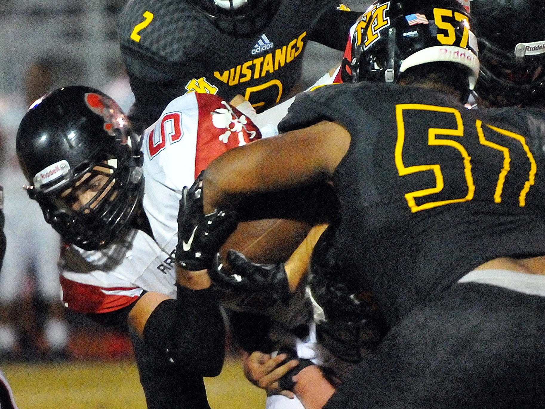 Merritt Island High's Brandon Montanez (57) rips the ball from Palm Bay High's Jared Morris.