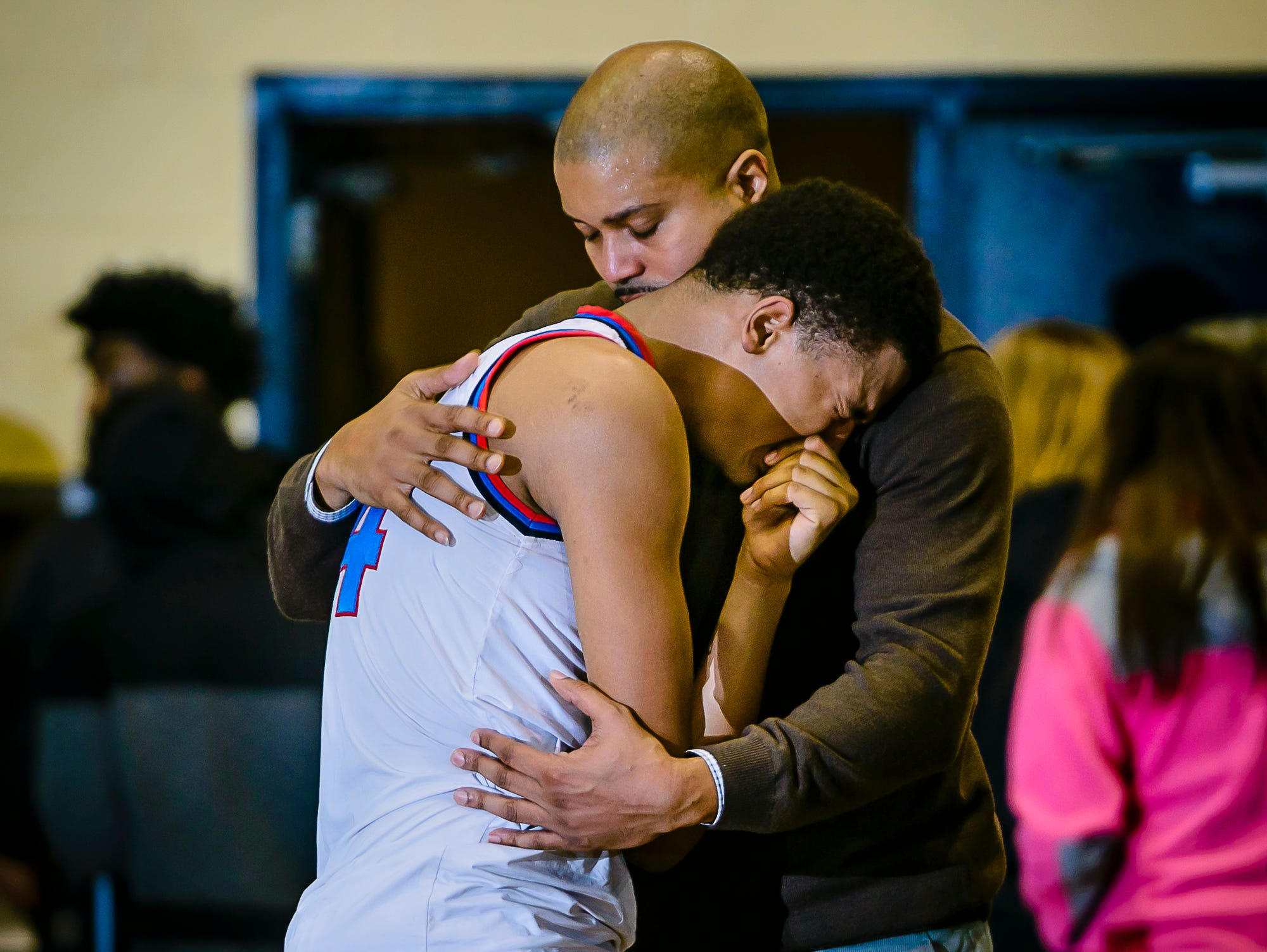Everett Head Boys Basketball Coach Desmond Ferguson ,right, hugs Diego Robinson after their Class A district final loss to East Lansing Friday March 10, 2017 at Don Johnson Fieldhouse in Lansing. KEVIN W. FOWLER PHOTO