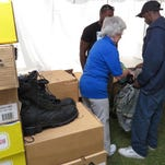Volunteer Sharyl Sheftz helps army veteran Eric Griffin find a new pair of shoes during the Homeless Veterans Stand Down behind the Gulf Coast VA's Joint Ambulatory Care Center.