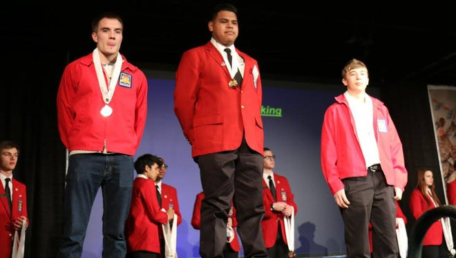 Eduardo Zamorano (center), a senior at Vineland High School, receives his gold medal for placing first overall in the SkillsUSA State Leadership Conference and Competition.