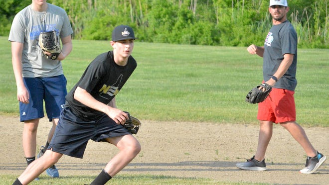 Dover's Gavin Hills gets ready to field a ground ball during his North East Baseball practice at Governor Weare Field in Hampton Falls on Thursday. Teammate Andrew Wertz of Dover, left, and NEB coach Tommy Lawrence look on.
