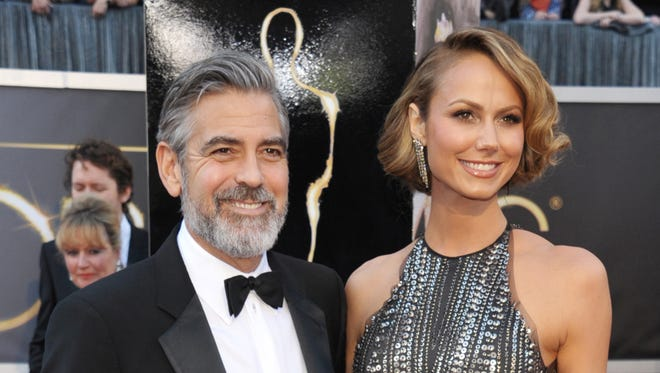 Actor George Clooney, left, and Stacy Keibler arrive at the Oscars at the Dolby Theatre in Los Angeles. Clooney, 52, Hollywood?s most determined bachelor famous for a litany of fleeting loves, including Keibler, has taken himself off the romantic market and proposed to 36-year-old attorney, Amal Alamuddin.