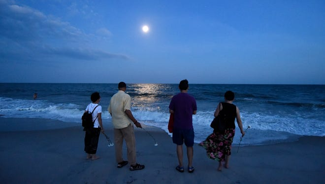 Mourners toss roses into the Atlantic Ocean after the 20th anniversary memorial of the TWA Flight 800 plane crash at Smith Point County Park on Sunday, July 17, 2016, in Shirley, N.Y.