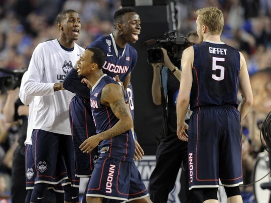 Kentan Facey, Ryan Boatright, Amida Bromah and Niels Giffey are elated at the buzzer as the Connecticut Huskies beat the Florida Gators 63-53 in the first semifinal game of the Final Four at AT&T Stadium Saturday, April 5, 2014 in Arlington, Texas. (Stephen Dunn/Hartford Courant/MCT)