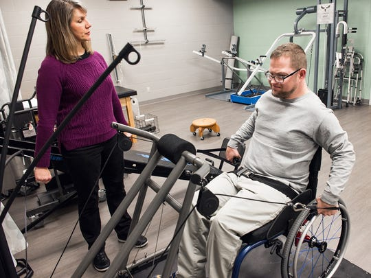 Andy Imlay, the adult ambassador for the Easterseals, works hard during therapy session with Easterseals Rehabilitation Center Physical Therapist Anne Byrne.