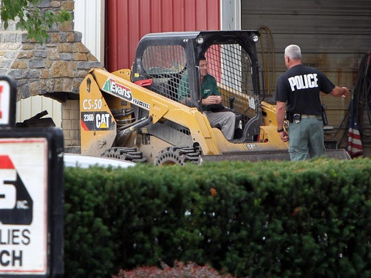 A police officer talks to an equipment operator at Evans Landscaping's Newtown location. The landscaping company raided by FBI agents earlier this month is enmeshed in a lawsuit alleging fraud involving a contract with a minority-owned business on public projects.