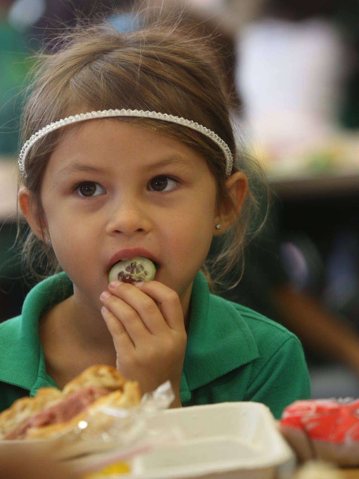 A student at Cahuilla Elementary School eats a cucumber that was harvested in an organic farm in Redlands.