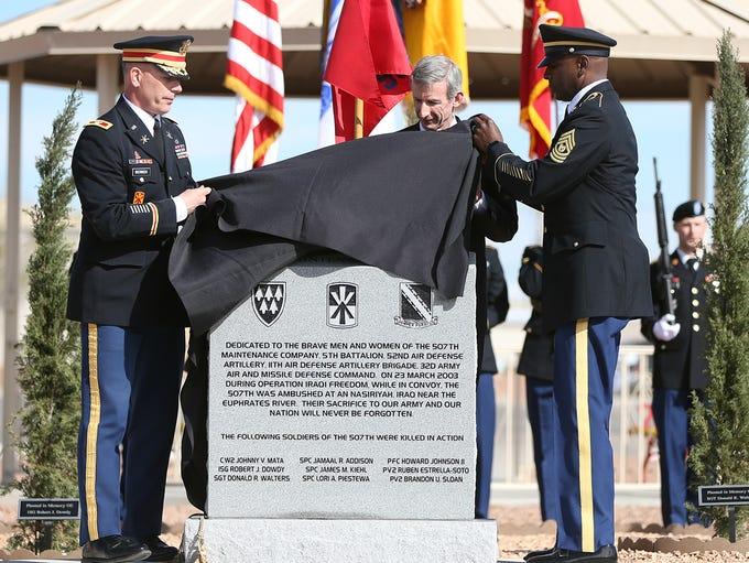 Retired Lt. Gen. Howard B. Bromberg, center, helps