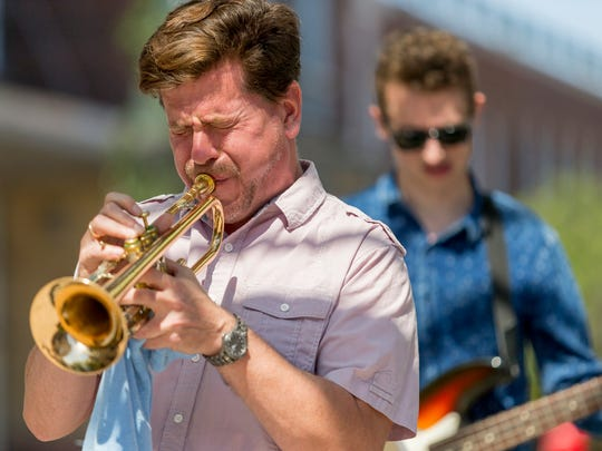 Paul Merrill, the director of jazz ensembles at Cornell University, performs with a group of students Saturday afternoon at the CU Downtown event.