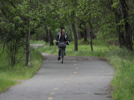 Tanya Boettcher rides her bike Thursday along the Sacramento