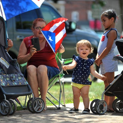 Elisianna Campos, 15-months-old, waves a Puerto Rican