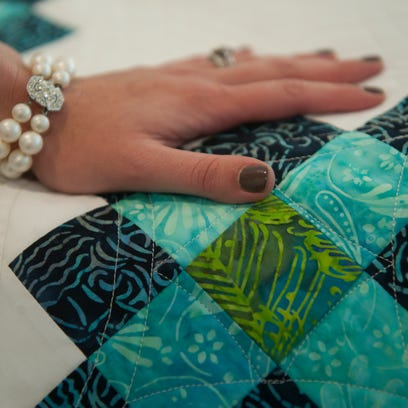 """Jessica Hreno touches the """"Two Sisters"""" quilt at the"""