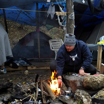 Kevin Hicks puts up a small Christmas tree in his tent