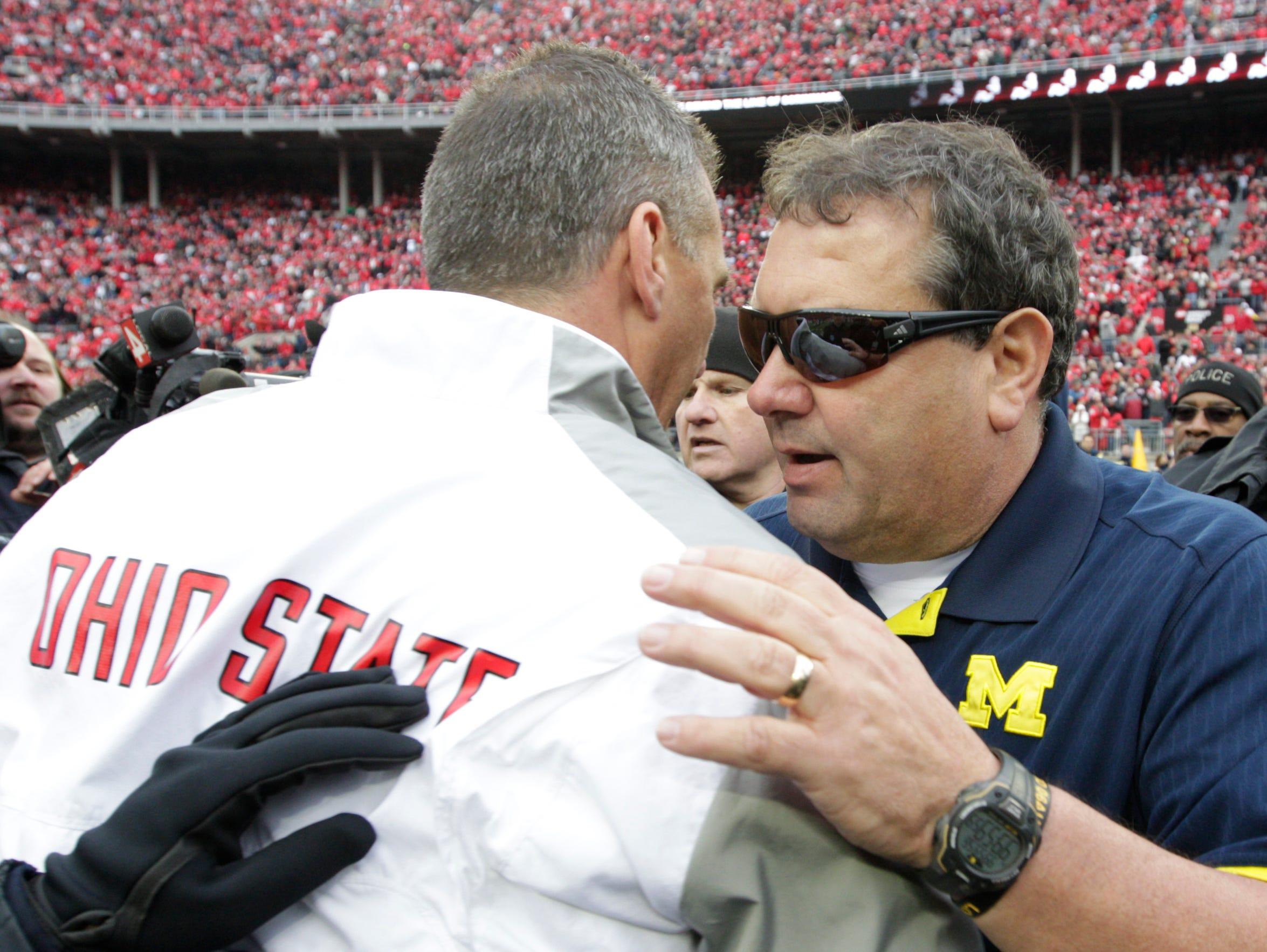 Brady Hoke, right, shakes hands with Ohio State head