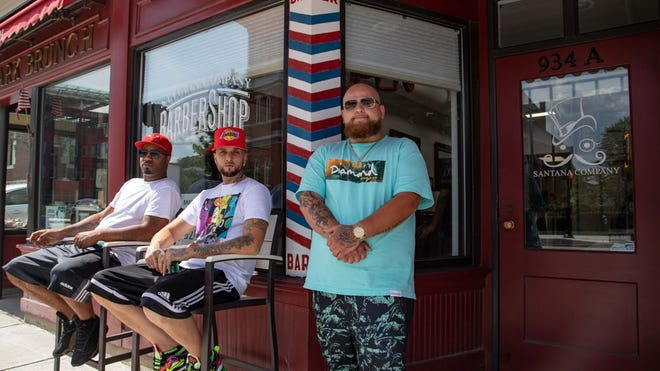 Ryan Seger, right, pictured in front of his barbershop next to Clark University's campus, said the sudden exodus of students this spring was alarming to his business.