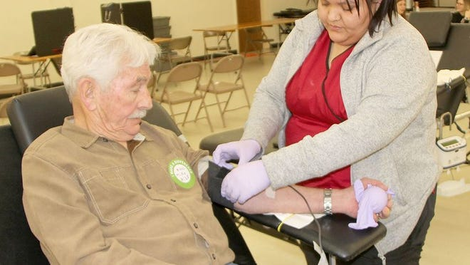 Blood donor Mike Martin watches as Red Cross phlebotomist Jessica Castillo completes the donation process at the blood drive on Tuesday at the Community Center.
