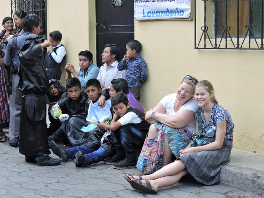 Meg Keilbach and Abby Overstrom watch the Good Friday processions with a host of new friends. The Lansing Youth Mission sent two groups to San Lucas Toliman, Guatemala, this year.