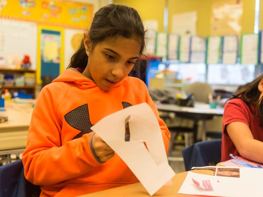 D'Ippolito third grader Nicole Ortiz decorates a poster for a pajama drive for underpriviledged children at D'Ippolito Elementary School on Monday, November 13.