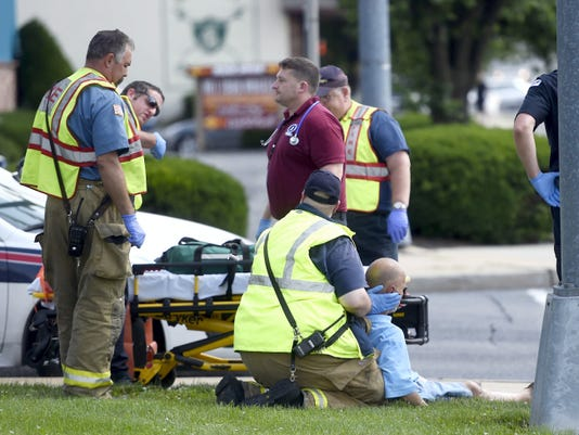 Rescue crews help an unidentified man who was struck by a car around 3 p.m. Friday at Chestnut and 12th streets in Lebanon. The car reportedly left the sence after the crash.