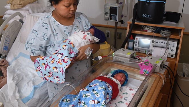 Lisa Murdock poses with her newborn twins Lindi Murdock, left, and Carter Murdock, who were born just the day before, on Thursday at the San Juan Regional Medical Center. The twins were bundled in Christmas stockings made by Crafty Creations, a service group that is part of the San Juan Regional Medical Center Auxiliary.