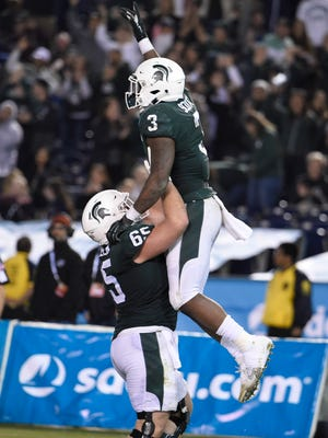 Michigan State running back LJ Scott (3) celebrates with offensive lineman Brian Allen (65) after scoring a touchdown during second half of the Holiday Bowl NCAA college football game against Washington State on Thursday, Dec. 28, 2017, in San Diego.