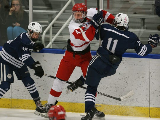 Penfield's Jack Schlifke (4) fights through Pittsford's Patrick Compare (11) and Zach Gmerek (18) for the puck during a game last season. The Patriots and Panthers could both be contenders in Class A this season.