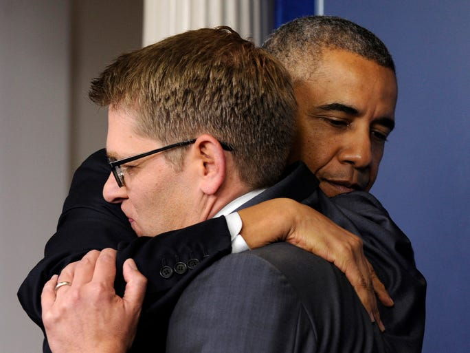 President Obama gives White House press secretary Jay Carney a hug after announcing that Carney will step down later next month during a surprise visit to the Brady Press Briefing Room of the White House on Friday. Obama said principal deputy press secretary Josh Earnest will take over the job.