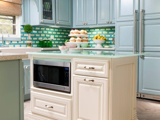 In this photo provided by HGTV, HGTV Designer and host of HGTV?s Great Rooms Meg Caswell used crisp, colorful blue green and white fused glass tiles to create a dynamic backsplash in this kitchen. The look is a good blend of contemporary and traditional. (AP Photo/HGTV)