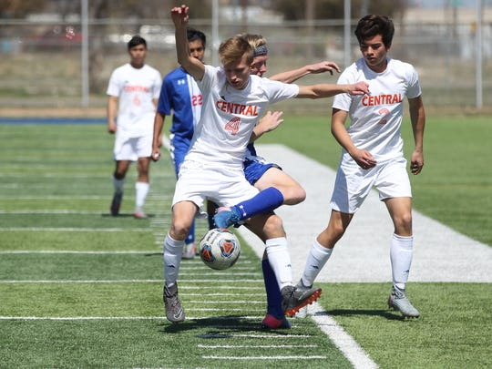 San Angelo Central High School's Triston Hill (4) gets tangled up with a Waco Midway player while trying to possess the ball in the District 8-6A soccer finale at Old Bobcat Stadium on Tuesday, March 13, 2018. Central's A.J. Alvarez looks on.
