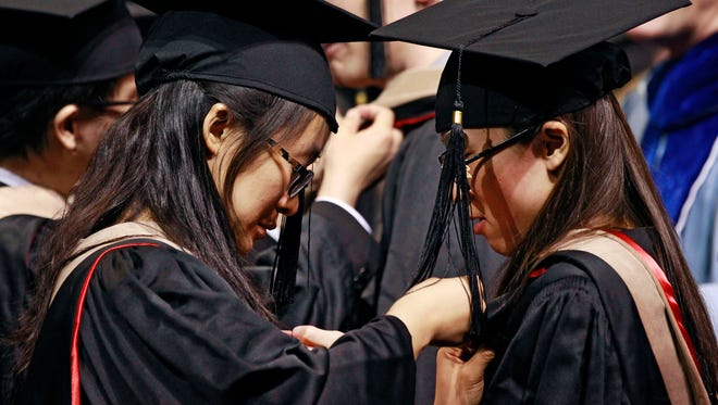 Students earning graduate degrees from Denver University wear caps and gowns as they pin graduation pins on one another during their commencement ceremony June 7.