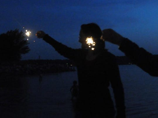 "Cameron Baye of Oneida and friends light up sparklers on the beach at Sunset Park in Sturgeon Bay as they await last year's ""Sturgeon Bay Celebrates!"" fireworks show."