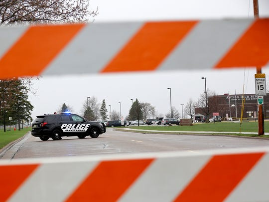 A police car sits guard outside Antigo High School,
