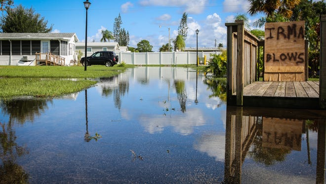 """A sign that reads: """"Irma blows"""" sits on a flooded street in Lake San Marino RV resort in North Naples as seen on Tuesday, Sept. 12, 2017. Many people wrote messages to Irma on their boarded-up windows."""