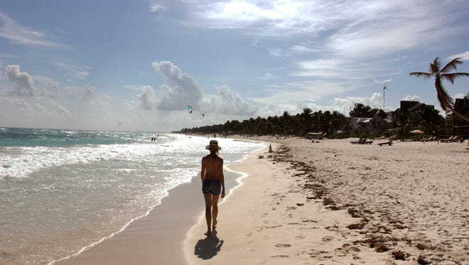In this Jan. 4, 2013, photo, a woman walks along the beach in Tulum, Mexico.