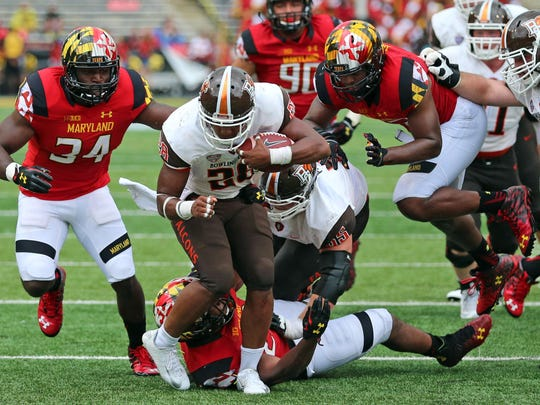 Bowling Green Falcons running back Fred Coppet (28) gains yardage before being tackled by diving Maryland Terrapins defensive back William Likely (4) at Byrd Stadium on Sept. 12.