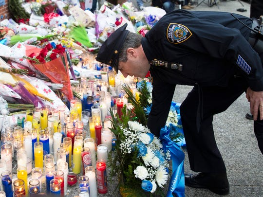 Patrick Lynch, president of the Patrolmen's Benevolent Association, places flowers Monday at a memorial for slain New York City officers Rafael Ramos and Wenjian Liu. New York Mayor Bill de Blasio on Monday called for an end to angry rhetoric between cops and protesters. Nation, 8A