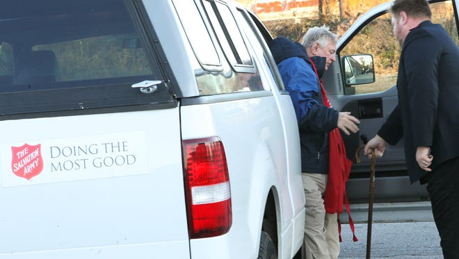 Lt. Robert Dolby, right, of the Salvation Army helps James White of Anderson get into position to ring a bell outside Quality Foods in Anderson for the Salvation Army.