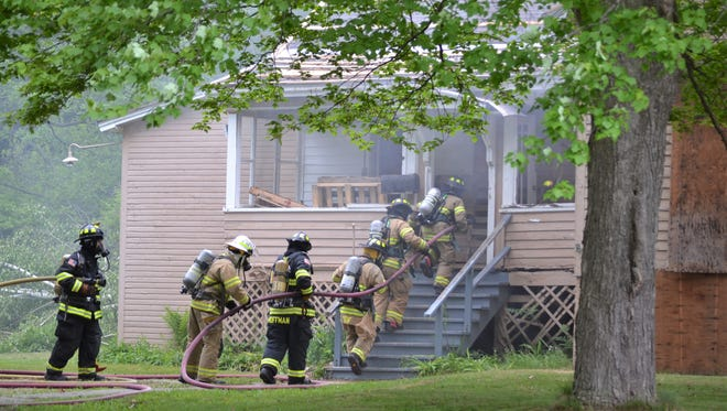 Firefighters move up the steps of a home on Hansen Avenue on Saturday as part of a live fire training excersise.