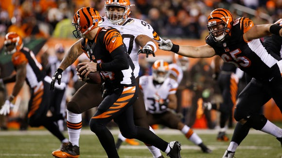 The Cincinnati Bengals quarterback Andy Dalton (14) is chased by the Cleveland Browns defensive end Billy Winn (90) as the guard Clint Boling (65) grabs a hold in the third quarter at Paul Brown Stadium.  The Enquirer/Jeff Swinger