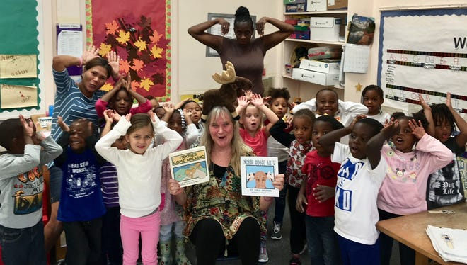 """Community Read Volunteer Cathy Woolsey, front and center, organizer of Indian River Arts & Concerts, is pictured with Head Start students during Indian River County Head Start's 2017 Community Read Week. Woolsey read two Arlo Guthrie books to the children: """"Mooses Come Walking,"""" and """"Whose Moose Am I?"""""""