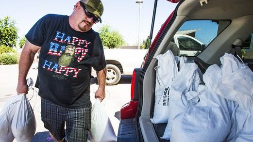 Matt Daley loads sandbags into his wife's vehicle at a Phoenix fire station in preparation for this week's predicted storm. Daley and his wife have been flooded out by the past three storms.