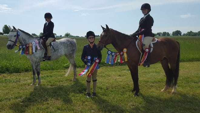 Caroline Smith (front left), Avery Newman and Mason Newman, all of Mountain Home, competed  successfully in the Northwest Arkansas Hunter Jumper Association Horse Show at Willow Springs Arena in Prairie Grove on May 8. Avery Newman, riding her Welsh Pony, Atlas, won the Reserve Championships in the Hunter and Equitation Intermediate Cross Rail Divisions. Mason Newman, also riding Atlas, won the Championship in the Beginner Cross Rail Hunter in the Division and the Reserve Championship in the Equitation Division. Caroline Smith, riding Diva, won the Championship in the Beginner Cross Rail Hunter Division.