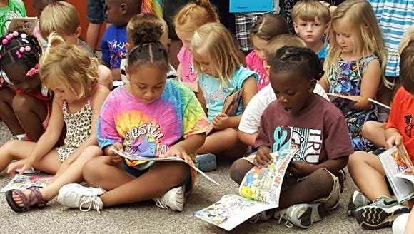 Pine Level Pre-K students pore over books donated by