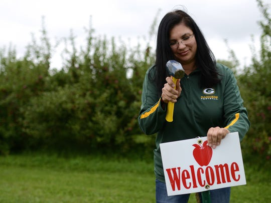 Michelle Danforth, tourism director for the Oneida Tribe of Indians, puts up welcome signs at the Oneida Apple Orchard.