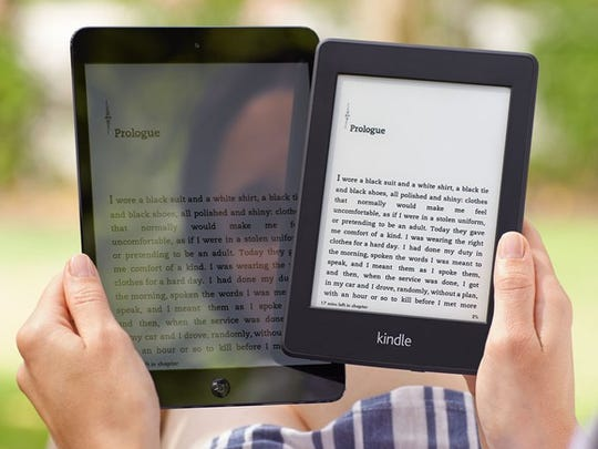 A woman's reflection is seen in a Kindle screen, as she holds it next to an Amazon Kindle Paperwhite, which shows no reflection.