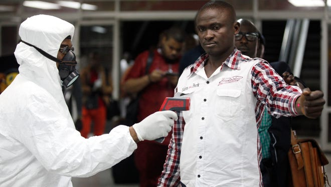 A Nigerian port health official uses a thermometer on a worker as a precaution against the Ebola virus at the arrivals hall of Murtala Muhammed International Airport in Lagos on Wednesday.